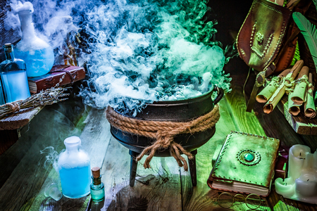 Mysterious witch pot with potions, books and scrolls for Halloween