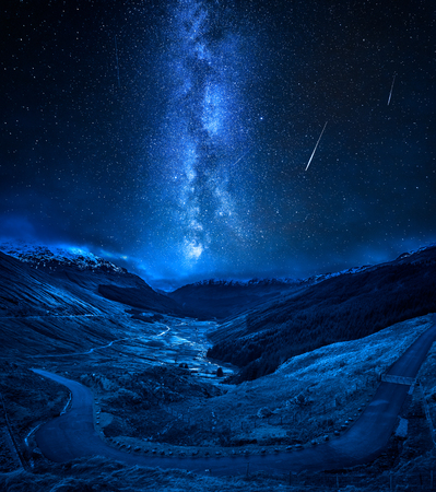 Winding mountain road over a canyon with falling stars