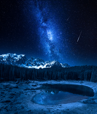 Milky way and falling stars over Carezza lake, Dolomites, Italy Stock Photo