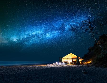 Playa con carpa brillante en la noche con estrellas fugaces