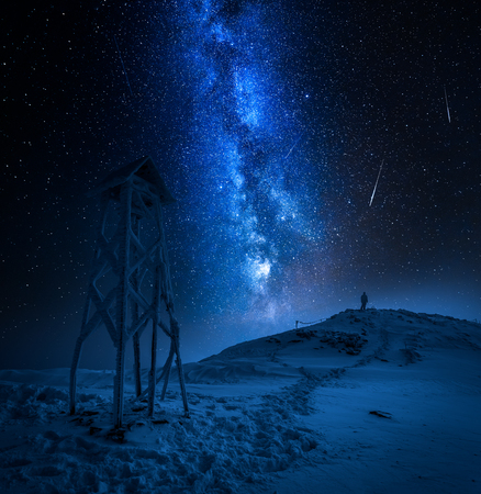 Man looking to falling stars in the mountain in winter Banco de Imagens