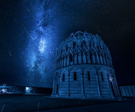 Milky way and falling stars over baptistery in Pisa, Italy Stock Photo