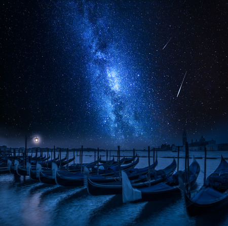 Milky way and falling stars over swinging gondolas in Venice