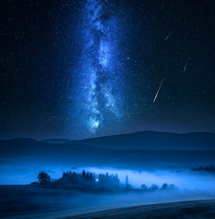 Small farm on field, milky way and falling stars