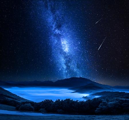 Milchstraße und Sternschnuppen über Bergen, Castelluccio, Umbrien, Italien