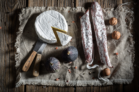 Fresh sausage, camembert cheese and fig on linen cloth