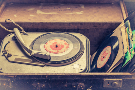 Tocadiscos clásico y vinilos en una vieja maleta