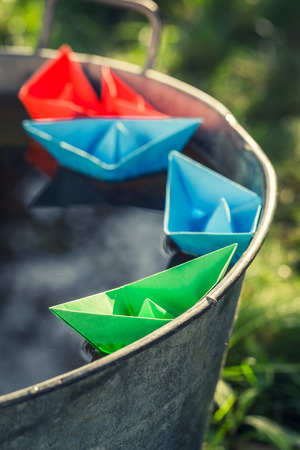 Origami paper boats as toned and filtered photo Stock Photo