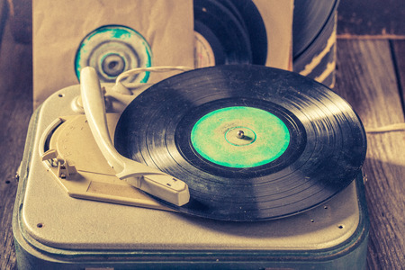 Vintage record player and vinyls as toned and filtered photo