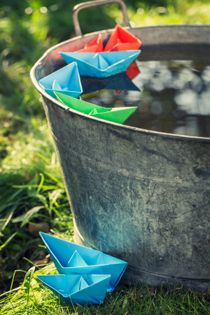 Small paper boats floating on water in washtube