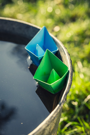 Handmade paper boats quietly floating on water in garden Stock Photo