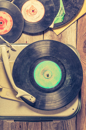 Old gramophone and few vinyl records on wooden table Stock Photo - 111007010