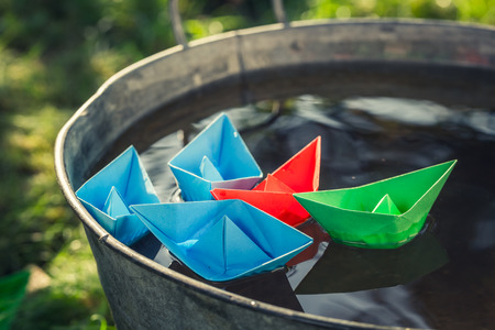 Handmade paper boats floating on water in washtube