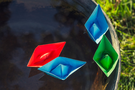 Small paper boats on water as unusual travel concept
