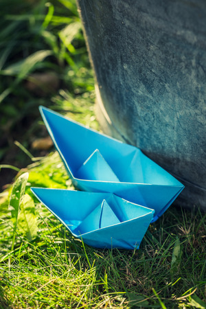 Two paper boats quietly floating on water in garden