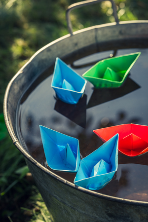 Origami paper boats on water as unusual travel concept