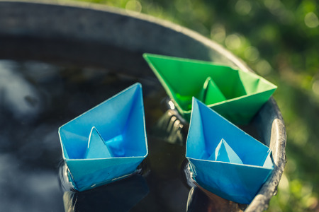Small blue paper boats as toned and filtered photo
