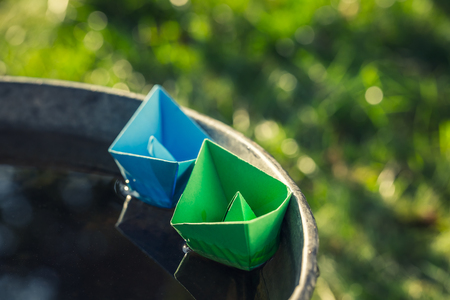 Origami paper boats floating on water in washtube