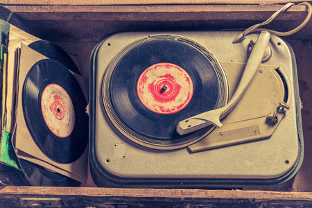 Old gramophone and stack of vinyl in an old suitcase