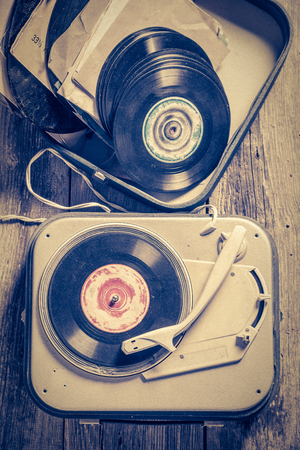 Top view of old gramophone and vinyls on wooden table