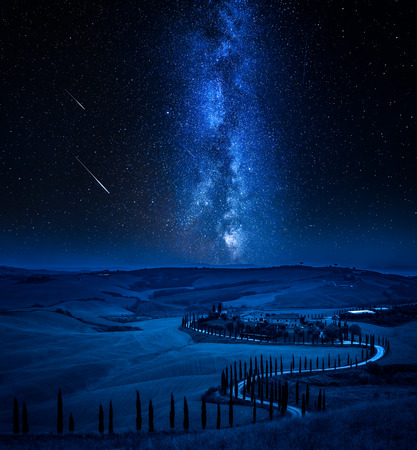 Milky way and winding road with cypressesin Italy Stock Photo