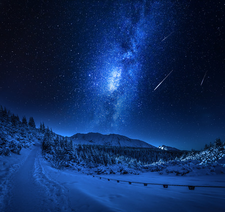 Mountain snowy path in winter with milky way, Tatars
