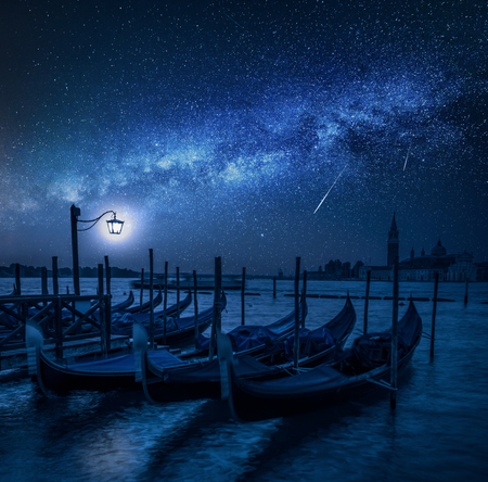 Swinging gondolas in Venice at night with stars, Italy