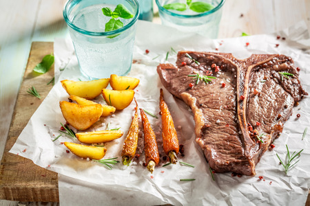 Homemade tbone steak served with water on white table Stok Fotoğraf