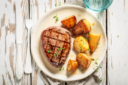 Delicious steak and roasted potatoes served with water on table