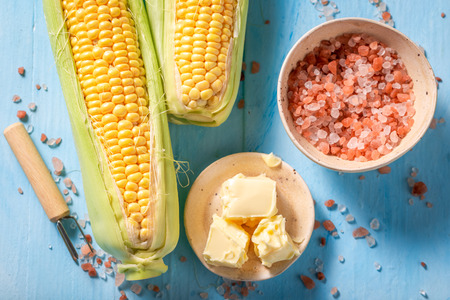Preparations for grilling sweet corncob with salt and butter Imagens
