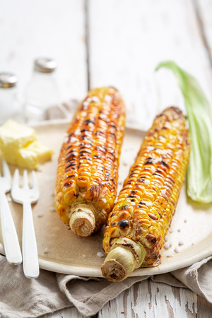 Grilled hot and delicious corncob with salt and butter Imagens