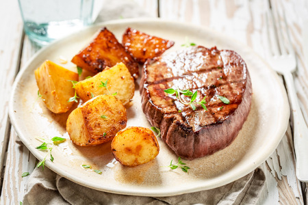 Fresh steak and roasted potatoes served with water on table