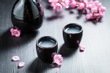 Closeup of sake in black ceramics and blooming flowers Banco de Imagens