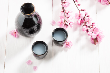 Top view of sake with flowers of blooming cherry 写真素材