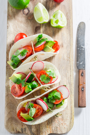 Top view of tasty tacos with cherry tomatoes and radish
