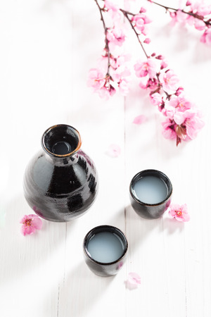 Sake in old black ceramics on white table 写真素材