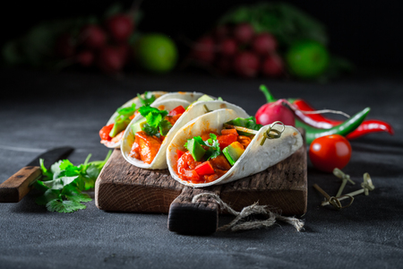 Tacos with spicy sauce and coriander on concrete table Stockfoto