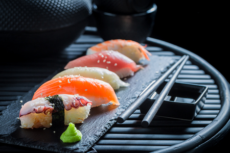 Delicious Nigiri sushi with rice and shrimp on dark table Фото со стока