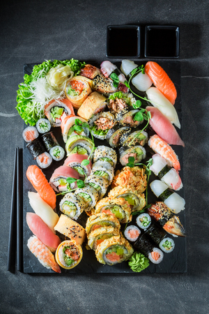 Healthy sushi mix with shrimps and rice on concrete table