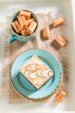Top view of toffee cake with bars on blue porcelain