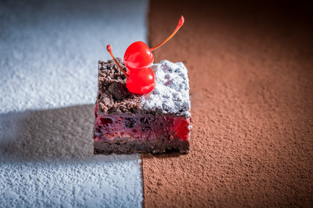 Closeup of delicious chocolate cake with crumble and cherry