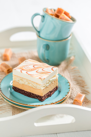 Closeup of toffee cake with fudge bars on blue porcelain