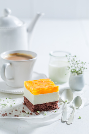 Closeup of cake with jelly peaches served with coffee
