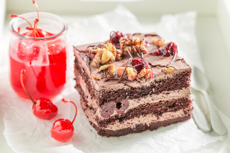 Closeup of sweet chocolate cake with walnuts and cherries