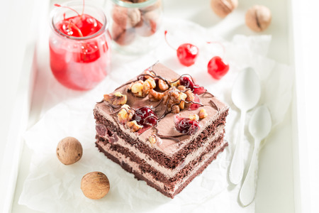 Chocolate cake with walnuts and cherry on white table Stock Photo