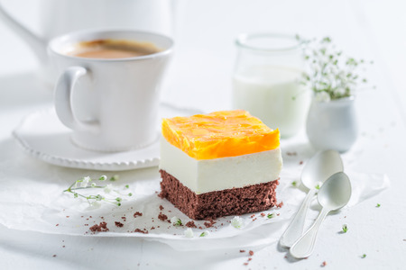 Closeup of delicious cake with jelly and served with coffee Stock Photo