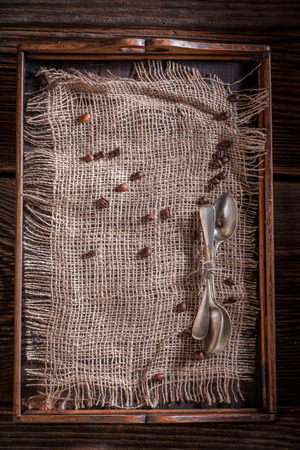 Old burlap doily and coffee beans on rustic wooden tray