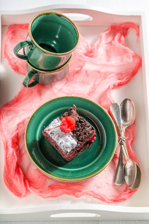 Sweet chocolate cake with cherry and crumble on green porcelain Stock Photo
