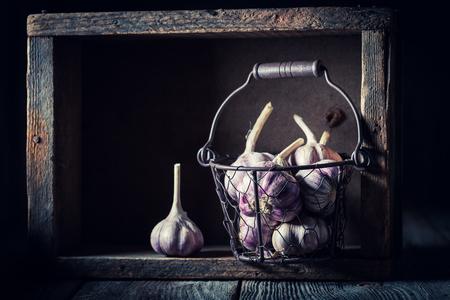 Aromatic rustic garlic in old metal basket Banco de Imagens