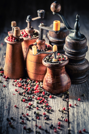 Old pepper mills with different types of pepper